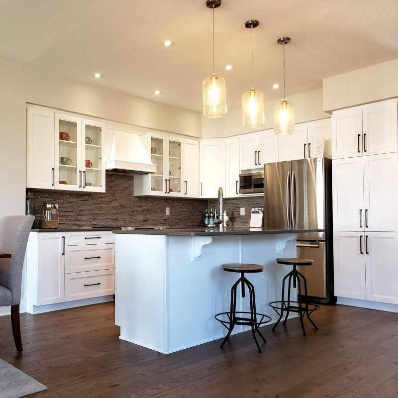 Full view of a renovated kitchen plan with new cupboards and mosaic tiled backsplash, hardwood floor