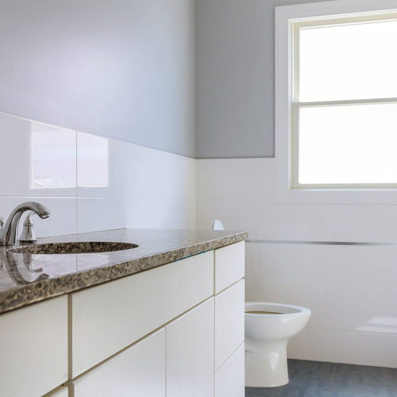 Master bath in new construction home with wood cabinetry large luxury white marble lined bathroom in